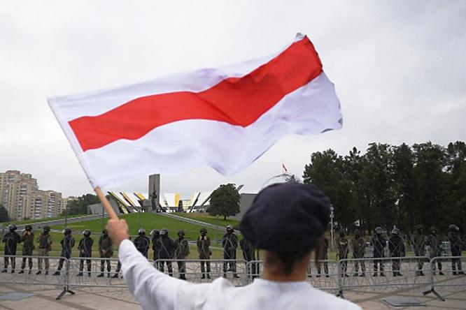 Участник акции протеста в Минске с флагом.